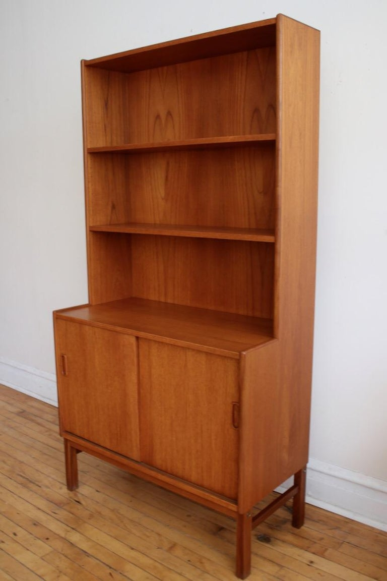 Mid-Century Modern Danish teakwood shelving unit. Just imported from Denmark! Beautiful woodgrain throughout. Adjustable shelving. Provides closed storage, countertop space and a display shelf in one compact unit. Excellent vintage