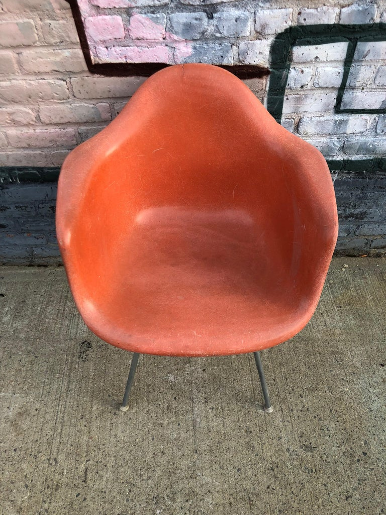 Vintage Herman Miller Eames fiberglass armchair in red orange. Embossed Herman Miller on authentic base. All mount and glides intact, circa 1960s.