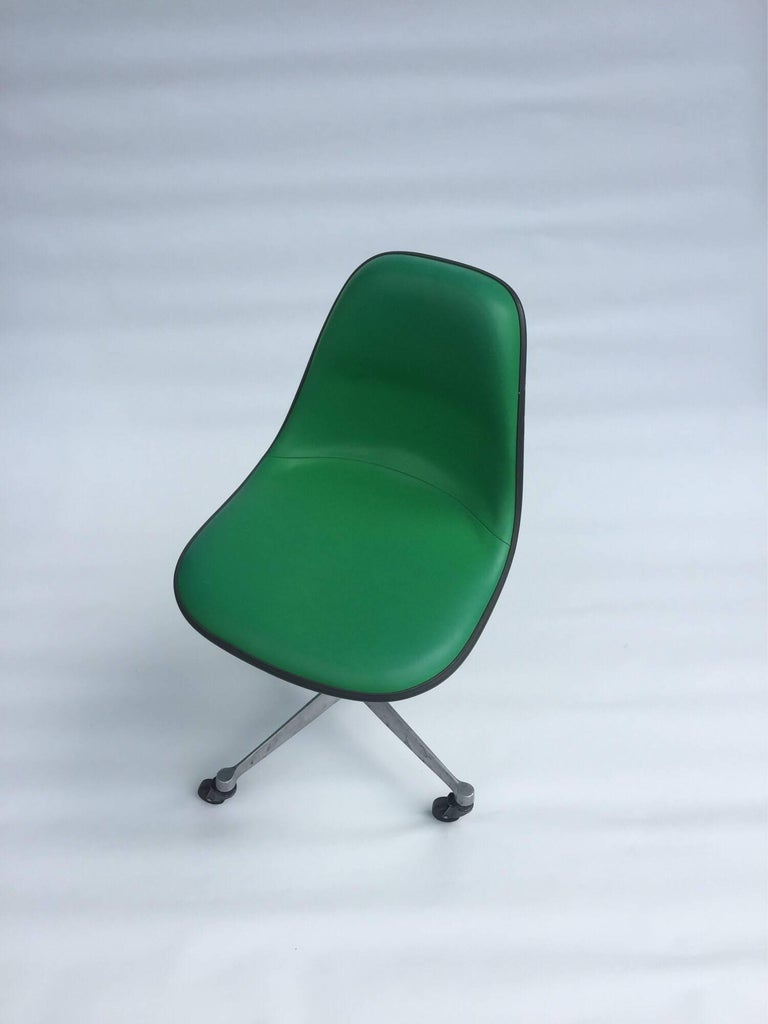 Kelly green fiberglass and vinyl Eames shell chair with rare back padded support on four point rolling office base. Similar to the PSCC chair. Chair is in good condition and the Kelly green color is vibrant and bright.