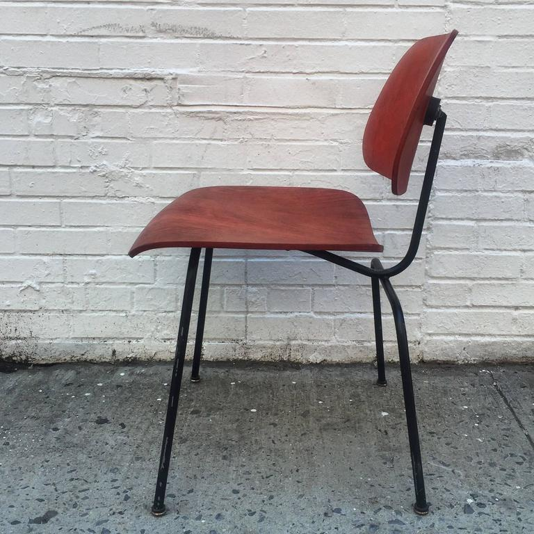 Early Herman Miller red DCM chair. Original black frame, mounts, glides and label. Excellent condition. Vibrant rich red aniline dye and lively birch grains. Mounts have not hardened.