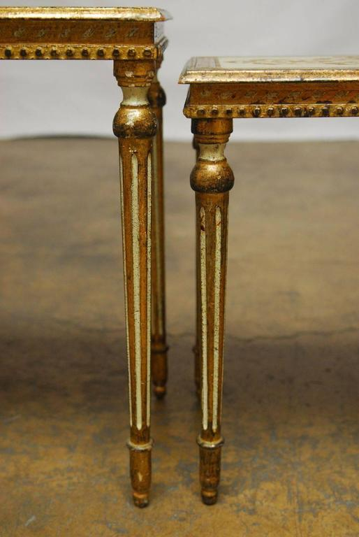 Set of lavish Italian nesting tables featuring Louis XVI style fluted legs and a hand applied gilt finish with a rich aged patina. Cream lacquer background on the tops with a foliate design and cream accents on the legs. Unique style, less common