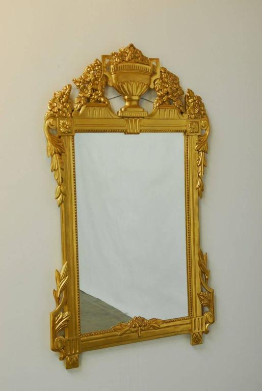 Remarkable French Regency gilt wall mirror made in the Louis XVI taste featuring a large sculpted urn form at the top. Beautiful bouquets of carved flowers and acanthus leaves are depicted on the top and sides. There are rosettes in the top corners
