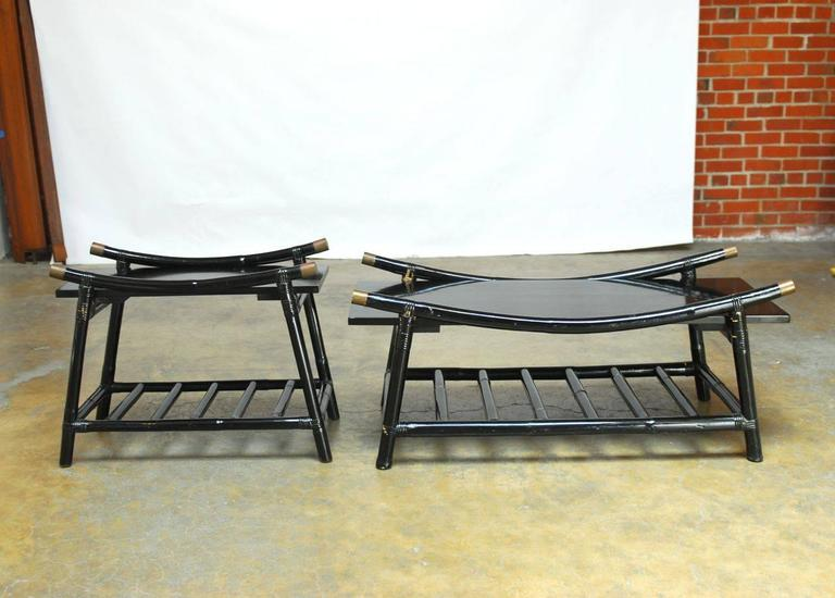 Ficks Reed Modern black lacquer rattan coffee table and side table with brass accent caps. Featuring ladder style magazine shelves and striking crescent form tops. Exceptional midcentury pieces that have a Japanese style bamboo construction.
