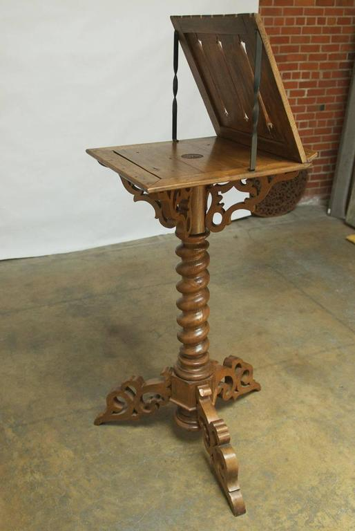 Large Italian Gothic church lectern made of hand-carved wood featuring a large rotating top section with scrolled supports atop a huge barley twist column. Supported by a scrolled tripartite base, this impressive display piece would be perfect in a