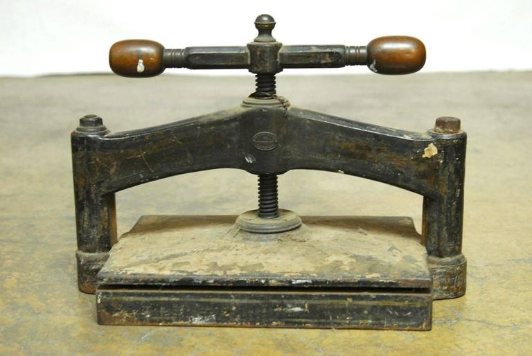 Remarkable English book press made by Hooper and Sons London, England. Solid cast iron construction that weighs 200 lbs. with rounded wooden handles. Makers label on front. Very impressive Industrial piece.