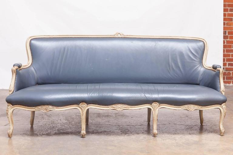 Stunning Louis XV style canapé sofa upholstered for William Gaylord in a French blue leather. Lovely painted frame with a distressed finish and accented by brass nail head trim. Rare serpentine seat supported by eight cabriole legs in the front and