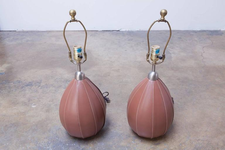 Rare designer lamps featuring top grade leather stitched covers over melon shaped bodies. Topped by brushed nickel covers and brass hardware with finials. No shades included.