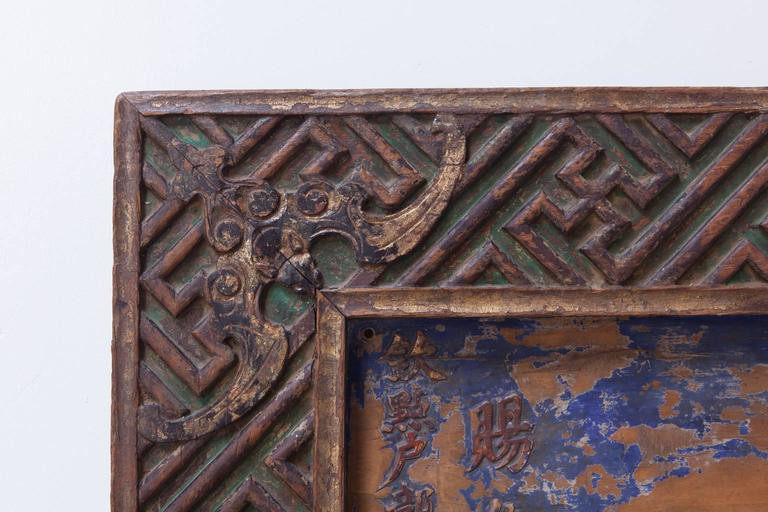 Remarkable Chinese honorary plaque featuring a large four character inscription and intricately carved geometric wan fret border with bats on all four corners and center. Traces of green lacquer pigment color still remain on borders with blue and