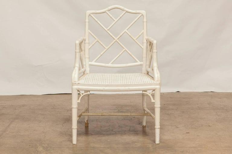 Elegant set of faux bamboo carved armchairs made in the Chinese Chippendale taste featuring a cane seat and a white lacquer finish. These armchairs have solid, tight joinery and a distressed paint finish. Made in the Classic style with open fretwork