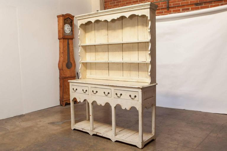 Rare Welsh dresser with a pot board base and an upper section having a molded cornice above a two shelf rack. The lower section is fronted by three drawers and a shaped apron. Supported by chamfered straight legs. The cupboard is constructed with