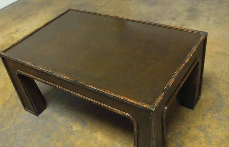 Unusual Chinese lacquered coffee table featuring a modern architectural design that has a rectangular shape top with sharp corners supported by substantial flared legs and deep green or brown in color.