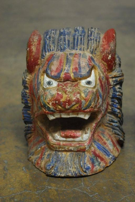 Colorful pair of Southeast Asian carved foo dog or foo lion roof ornament heads featuring a polychrome multi-color finish. Fierce expression and flowing hair, each is carved from one heavy piece of heart wood. Originally displayed on an asian
