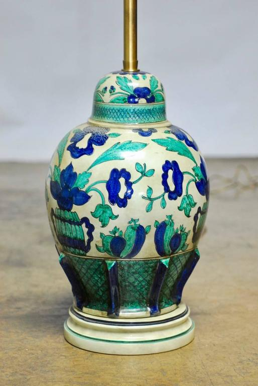 Large Italian ceramic lidded urn table lamp by Marbro Lamp Co. featuring a faience hand-painted body with Indigo blue flowers and foliage. Supported by a turned ceramic plinth and equipped with brass hardware and original milk glass diffuser. Signed