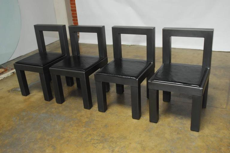 Ultra chic set of modern Industrial dining chairs artisan made from carbon steel. Featuring a dark gun metal grey anodized finish. Constructed from sheets of steel varying in thickness from 1/8th inch to 1/4th inch thick. Each chair weighs over