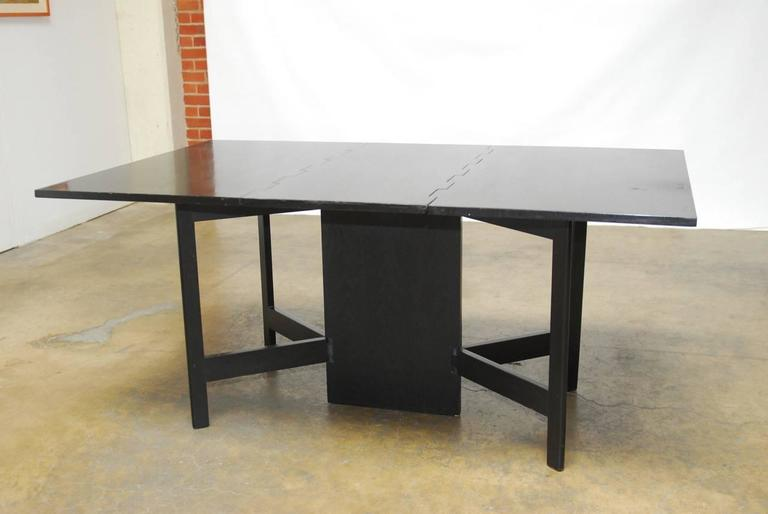 Rare Mid-Century drop-leaf or gate leg dining table designed by George Nelson and associates for Herman Miller. Features an ebonized walnut finish and a unique design that allow the legs to go into multiple configurations that could also serve as a