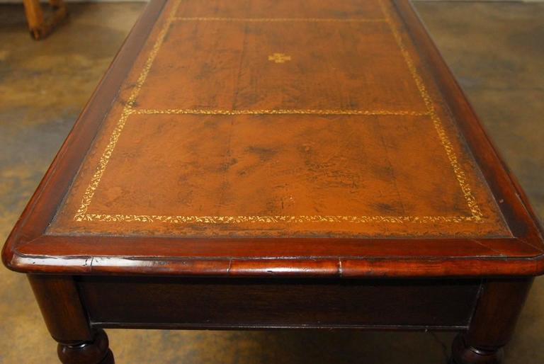 Handsome 19th century English Regency writing table executed in walnut featuring a tooled leather top with gilt decoration. Fronted by 2 drawers and supported by turned and fluted legs with brass caps on the feet. The table was purchased by the