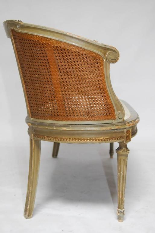 Elegant French Louis XVI cane settee or canape en corbeille. Featuring an intricately carved frame in a basket form with an hourglass window of floral swag design and double caned sides. Originally finished in a