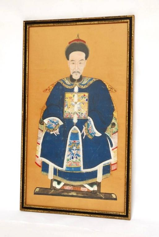 Colorful Chinese Qing dynasty ancestor portrait of a high ranking official or ruler depicted sitting with a beautifully embroidered robe decorated with rank badges. Bright colors are accented by gold leaf and mounted into a giltwood frame.