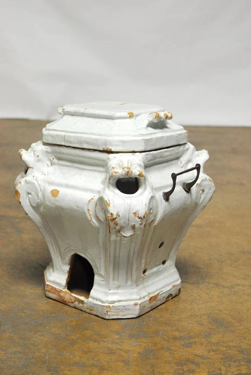 Featuring a large lidded body decorated with lion heads on each corner depicted with open mouths where heat escapes. This thick glazed ceramic urns has openings on each side large enough for hands and holes to ventilate air in the sides. Several