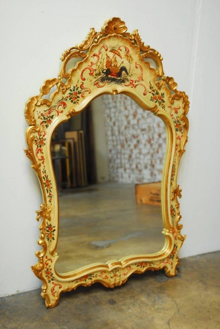 Stunning Italian Venetian style mirror decorated in the chinoiserie taste featuring a hand-carved frame finished with an ivory lacquer ground. Decorated with carved scrolls and surmounted by a shell crest. Hand-painted with an Asian motif and