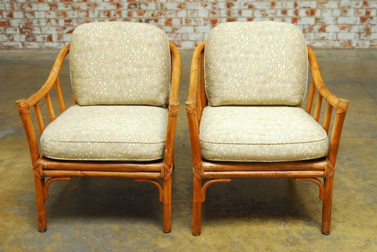 Classic pair of organic modern bamboo lounge chairs by McGuire. Featuring graceful bent bamboo arms with column supports and thick cushions. The frame is reinforced with leather rawhide strapping. Richly decorated modern McGuire fabric with a floral