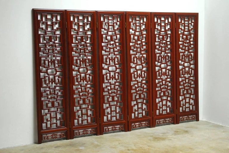 Fantastic Chinese six-panel Rosewood carved lattice folding screen. Features intricate geometric patterns with Greek key motif. Each panel is 17.5 inches wide and has a contrasting oval carved shape in the center and prosperity emblem carved between