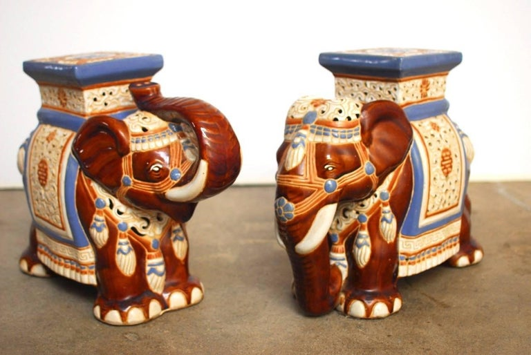 Playful pair of ceramic Asian elephant garden stools or drinks tables. Featuring caparisoned bodies with hand-painted saddles and costumes. One is depicted with its trunk up and the other is down. Vibrant colors with prosperity emblems on the seat