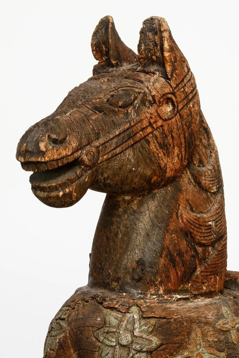 Charming carved wooden temple horse from India mounted on a wooden stand. Features an ornate distressed and faded polychrome finish of decorative carved flowers. Depicted standing with a saddle and bridle. Lovely wear and distressed finish.