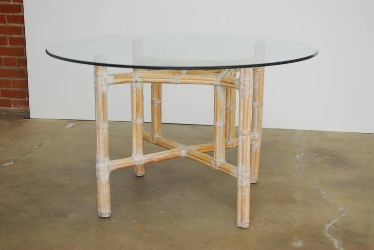 Round organic modern bamboo and rattan dining table by McGuire. Constructed from a bamboo wrapped metal skeleton and reinforced with McGuire's trademark leather rawhide strapping. The natural rattan has been finished with a whitewash and is topped