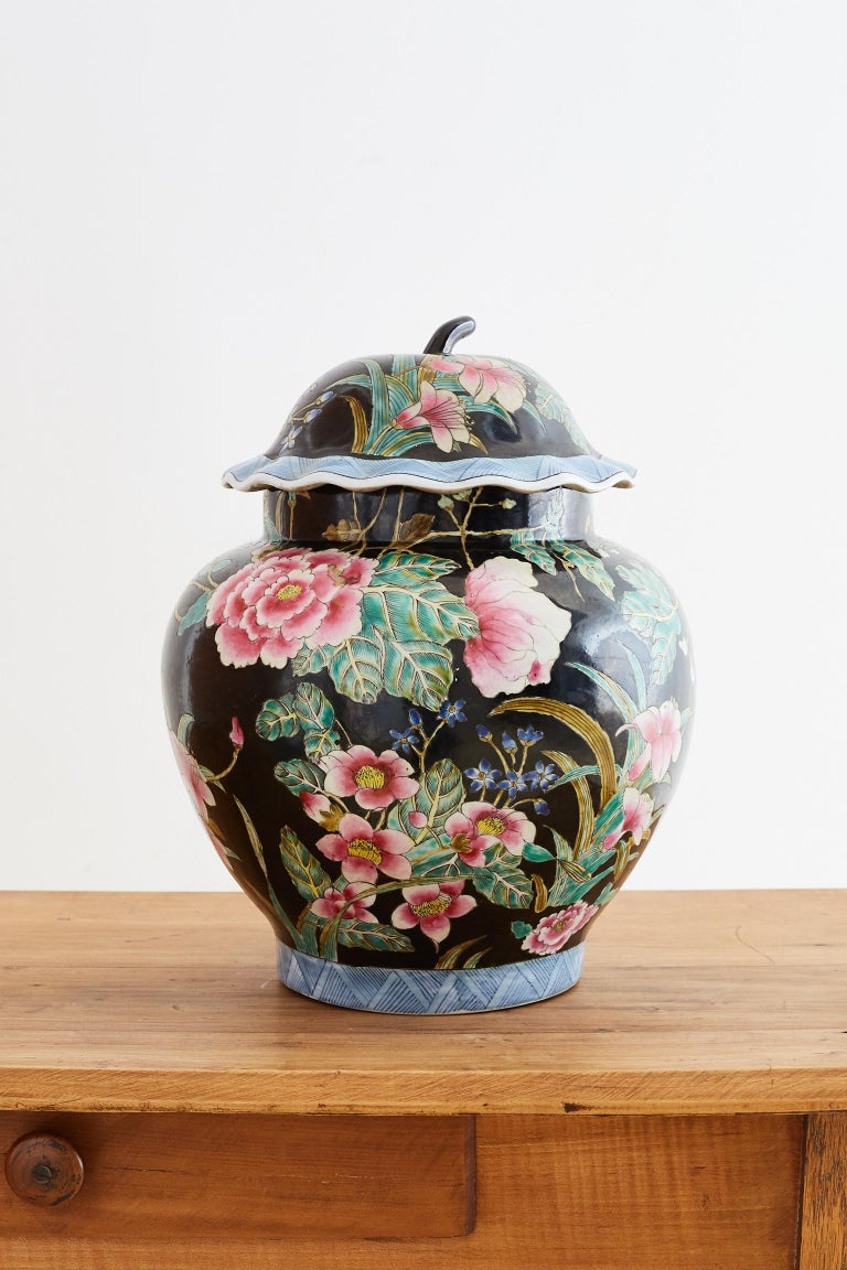 Colorful Chinese export famille noir porcelain ginger jar. Features an array of Famille Rose colors over a black ground with a matching lid. The lid and bottom of vase have a blue and white geometric pattern. The jar is decorated with floral and