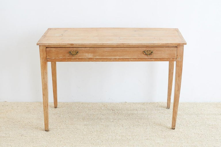 Rustic 19th century writing table or desk made from American pine. Handmade dovetail construction fronted by one large drawer with brass pulls. Perfectly cut drawer that slides easily. Supported by elegant tapered legs. Beautiful natural wax finish
