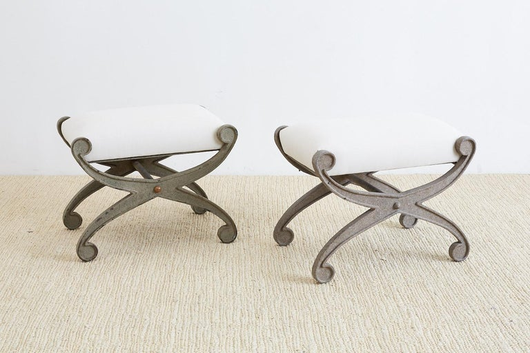 Amazing pair of curule iron benches or stools having an x form. Features a heavy, solid iron base with a lovely distressed patina and new cream upholstery. Custom made by a foundry in Los Angeles, CA.