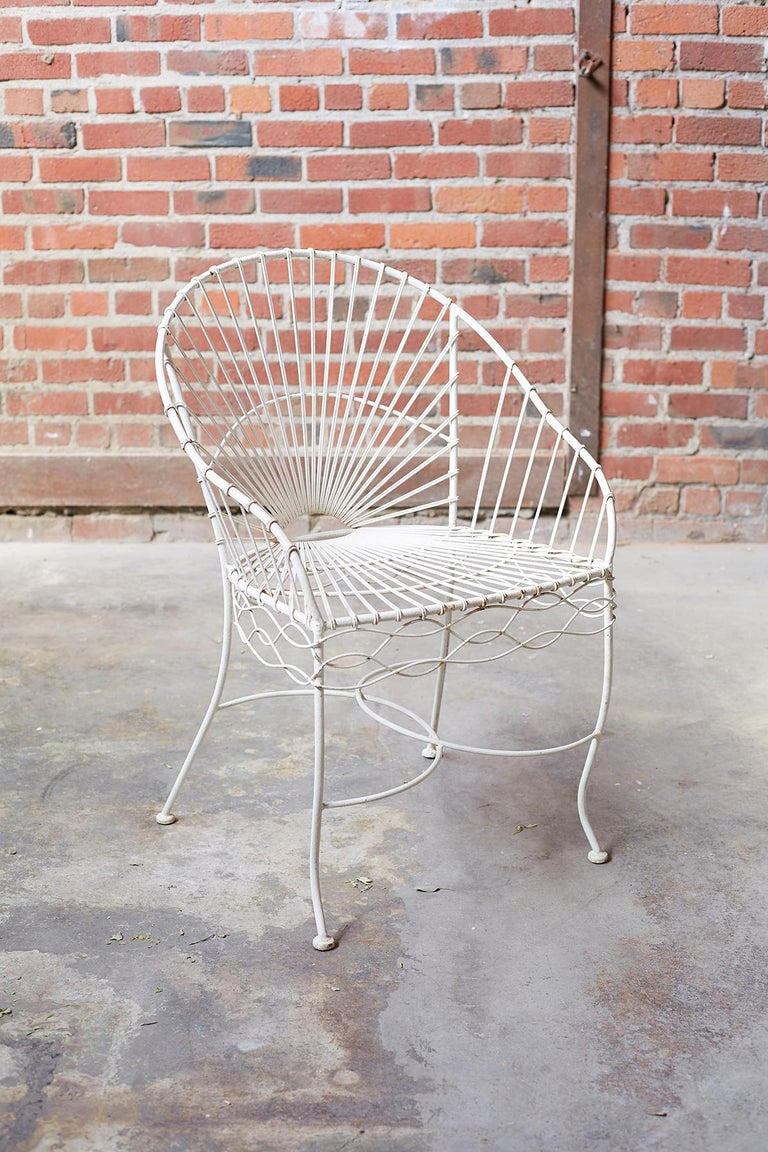 Fabulous set of six French painted iron and wire garden patio chairs. Featuring an iron frame decorated with twisted wire in a sunburst pattern on the back and seat. The sides have a wavy wire decoration and the legs are conjoined by overlapping C