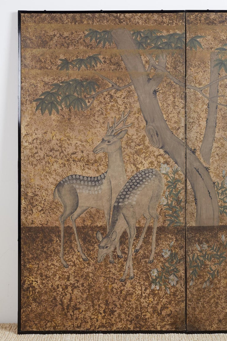 Captivating Japanese two-panel Showa period screen depicting three Japanese Sika deer in foliage under a tree. Beautifully textured painting with layers of gilt colors and patterns. Colorful blue flowers arising on the forest floor and a green