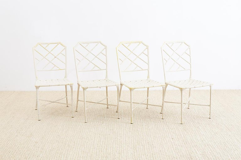 Set of four Palm Beach style brown Jordan Calcutta garden or patio chairs featuring a faux bamboo painted aluminum frame made in a Chinese chippendale style. Each chair has a basket woven design seat and tapered legs with cross stretchers.