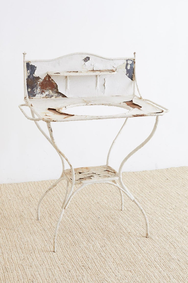 Beautifully distressed English Victorian wash stand or garden planter made of painted iron. Two-tier design with a backsplash having a small shelf. Towel racks on both sides and supported by gracefully curved legs. No basin with a 14 inch diameter