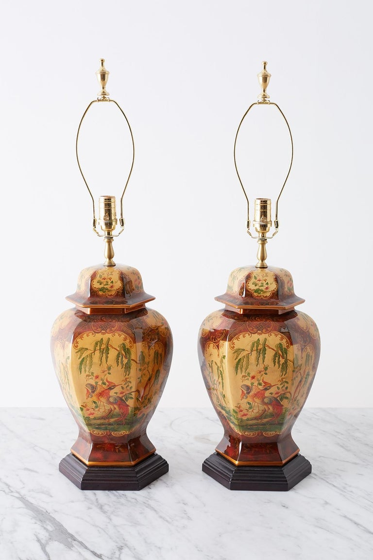 Exceptional pair of chinoiserie glazed ginger jar form table lamps by Bradburn Gallery. The jars having a hexagonal form with a conforming wood plinth. Each jar features beautifully decorated scenes with birds and trees. The urns are topped with