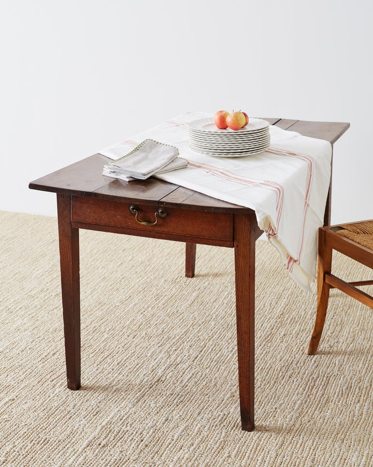 Rustic 19th century English farmhouse table or work table constructed from beautifully grained oak. Made in a simple style with a plank top and elegant tapered legs. One side of the table has a sliding drawer with a brass pull. Lovely profile and