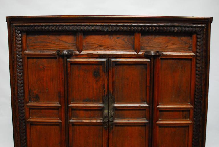 Large, Chinese two-door cabinet chest with a decorative carved front case featuring a Jacobean style border and a faux bamboo trim next to it. Two small doors open to a large open two shelf storage area. Mortise and tenon joinery throughout and