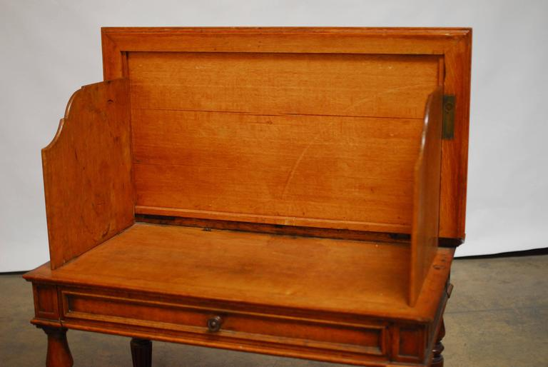 A rare 19th century English desk made of oak with a clam-shell top and side walls that lock into place with brass hardware. The carved privacy walls have a gentle curved edge and the case is fronted by one large drawer and a frame detailed case. The