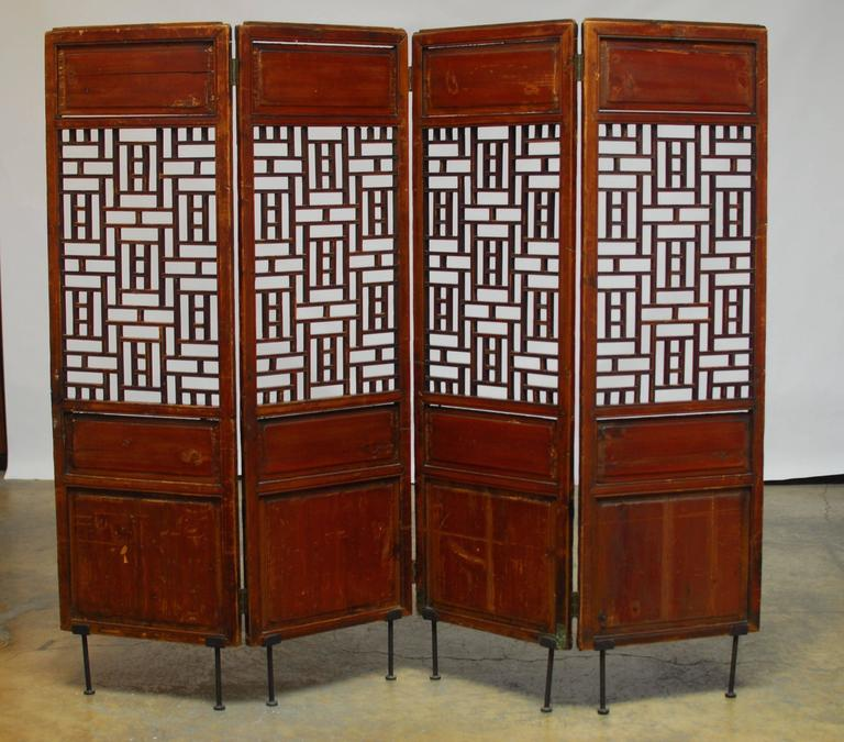 19th century Chinese screen featuring a geometric lattice window in each panel. Constructed with old world mortise and tenon joinery and mounted on iron feet. Originally four separate carved elm panels now joined and lifted for display.