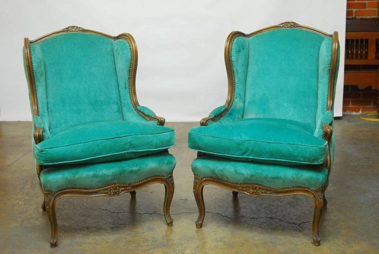 Impressive pair of French wingback armchairs made in the Louis XV taste featuring turquoise velvet upholstery with thick down filled cushion and finely carved frames with extended wings. Supported by cabriole legs and finished with brass nail head