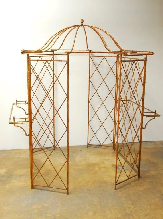 Fantastic Hollywood Regency gilt metal faux-bamboo garden gazebo featuring a pagoda roof with ten arm supports and topped with an acorn finial. Beautiful architectural element made of six panels with a cross hatch design and a 29