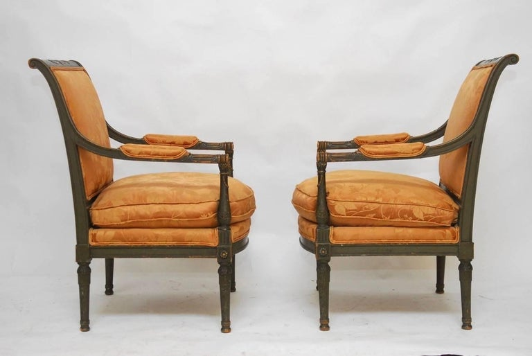 Rare pair of painted fauteuil armchairs made in the Directoire style featuring generous molded frames with a sweeping back. Carved in a neoclassical motif and supported by tapered column legs. Upholstered with a silk damask fabric in a rose gold
