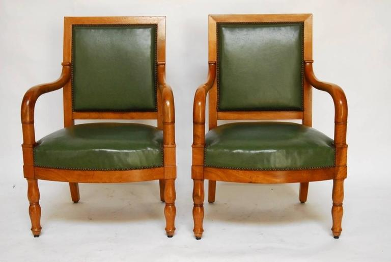 Impressive pair of French Empire Mahogany library chairs featuring square backs and gracefully curved arms that attach to a generous seat. Upholstered in a Napoleonic dark green with small brass nailhead trim. The chairs or fauteuils are supported