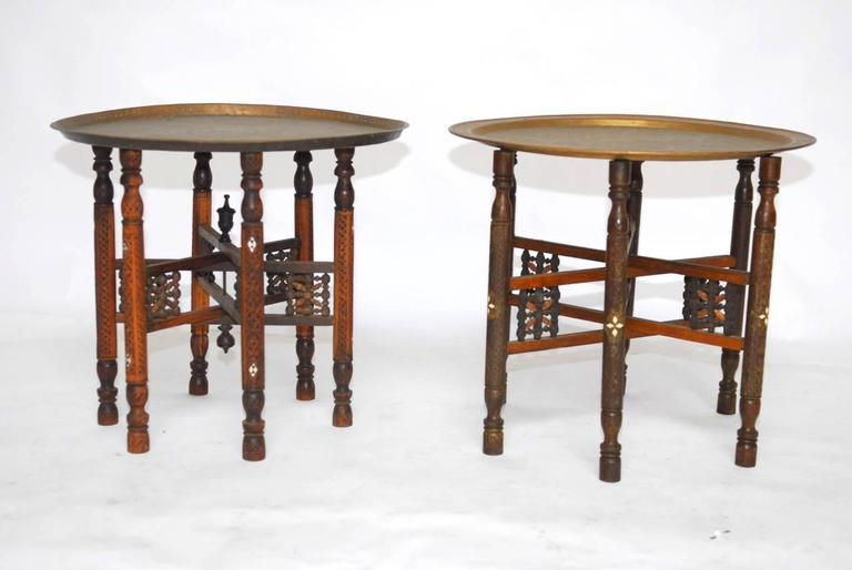 Traditional pair of Moroccan brass tray and inlaid wood folding drink tables. Featuring six-leg folding bases with intricate carved details and inlay. Topped with patinated etched brass tea trays. Each table base slightly varies in style and