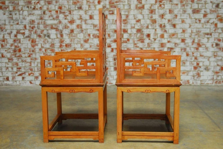 Stunning pair of Chinese carved hardwood armchairs made in the Ming style featuring an open fretwork Greek Key design, frame and an inset back splat with Dali marble and rich Huali rosewood inlay. These armchairs were made with generous proportions