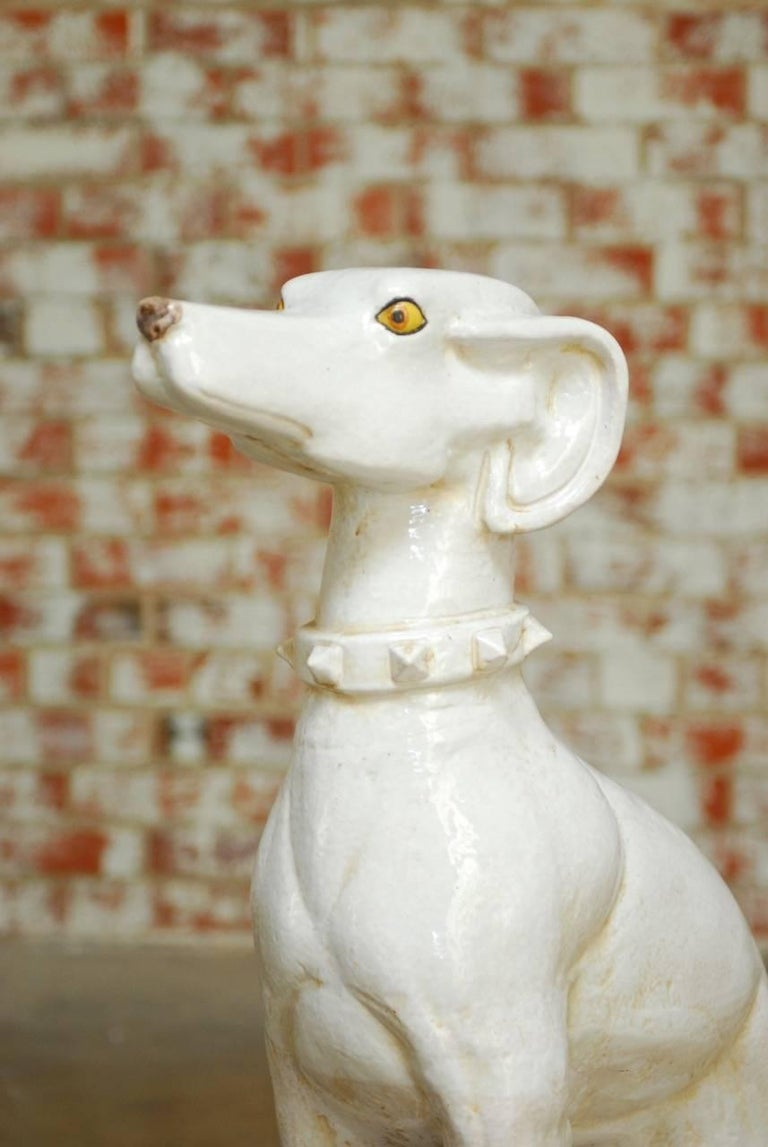 Monumental Mid-Century Italian glazed ceramic greyhound dog sculpture made in the Hollywood Regency taste. Beautifully glazed with a shiny textured body and a collar with spikes. Her head stands at attention featuring large ears and piercing yellow