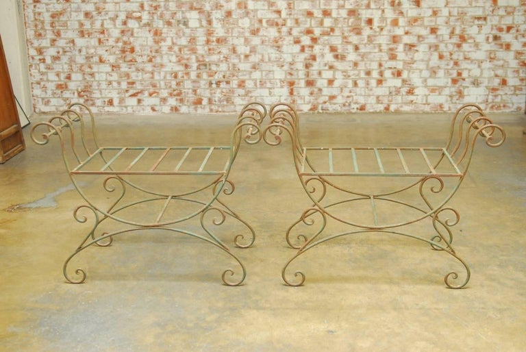 Stylish pair of Hollywood Regency wrought iron Curule benches made in the Neoclassical taste. Featuring an X-form design with scrolled arms and feet. The seats measure 25 inches wide and 18 inches deep and do not have cushions. These benches are