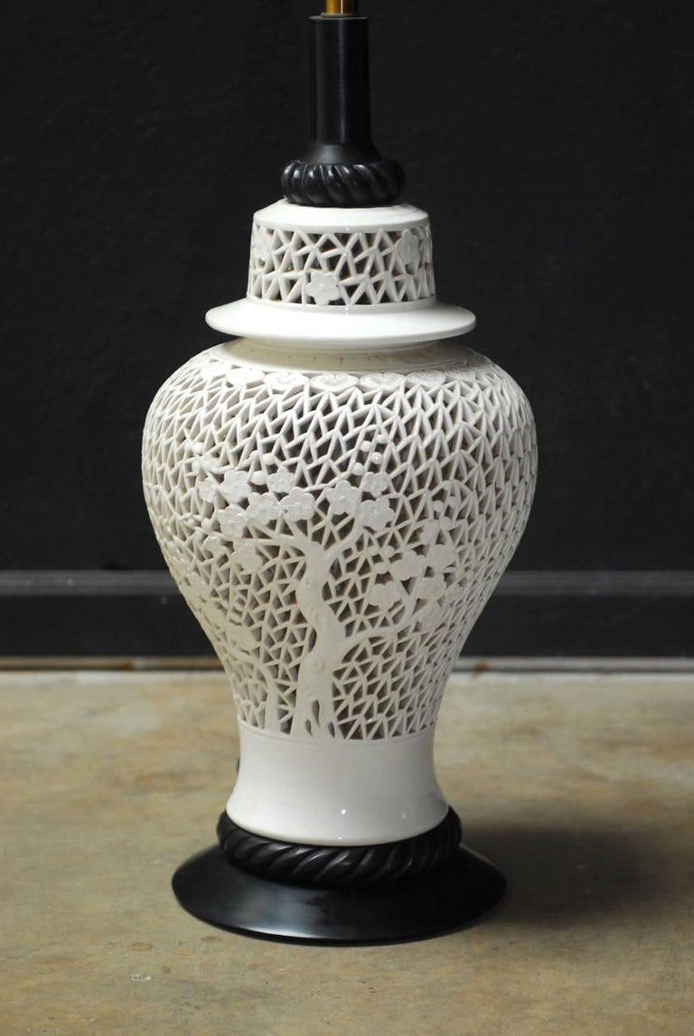 Large Mid-Century Modern Chinese blanc de chine porcelain table lamp in the form of a ginger jar vase. Featuring a pierced fretwork body of cherry blossom trees with a matching lid. Mounted on an ebonized wood base with brass hardware. Unusual large